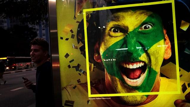 Werbeplakat an einer Plakatsäule: Zu sehen ist die Grossaufnahme eines Fans, der sein Gesicht mit den brasilianischen Farben bemalt hat.