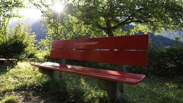 Bank mit Aufschrift Gemeinde Schattdorf. Es ist sonnig, aber die Bank ist im Schatten.