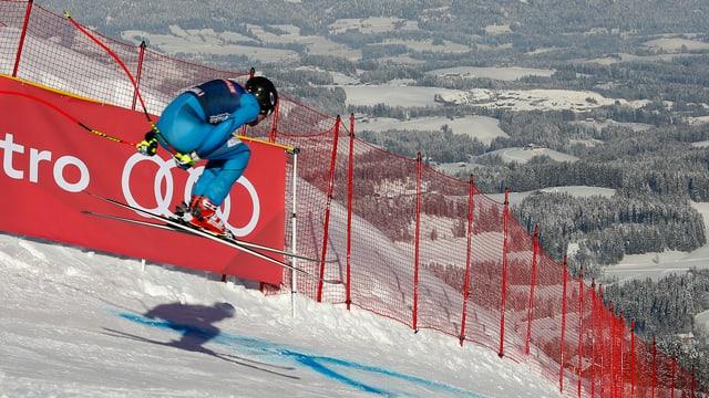 Ein Skifahrer springt in Kitzbühel über die Hauskante