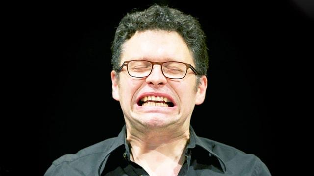 Ein Mann mit kurzen braunen Haaren und Brille spannt sein Gesicht stark an.
