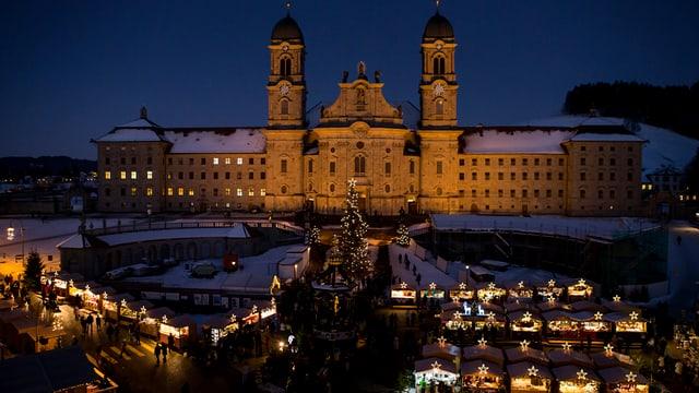 Ein grosses Kloster, davor leuchten die Lichter eines Weihnachtsmarktes.
