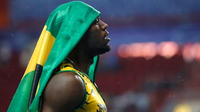 Usain Bolt nach seinem Sieg an den Weltmeisterschaften in Moskau. Er hat sich die jamaikanische Flagge über den Kopf gehängt.