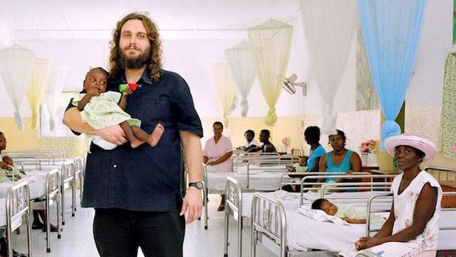 Eine Bettenstation der Hilfsorganisation «Terre des hommes»: Ein dicker weisser Mann steht in der Mitte und hält ein kleines unterernährtes schwarzes Mädchen auf dem Arm.