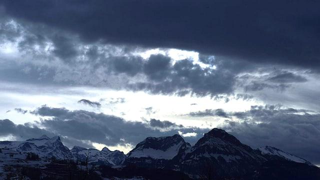 Blick an einen winterlichen Bergkamm. Düstere, schwarzgraue Wolken türmen sich über den Gipfeln.