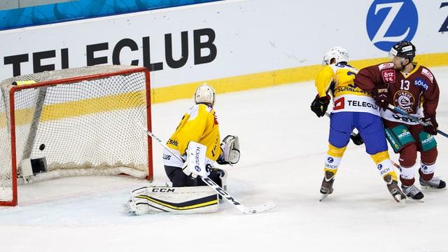 Giugaders da hockey miran sin il puck ch'è en il gol.