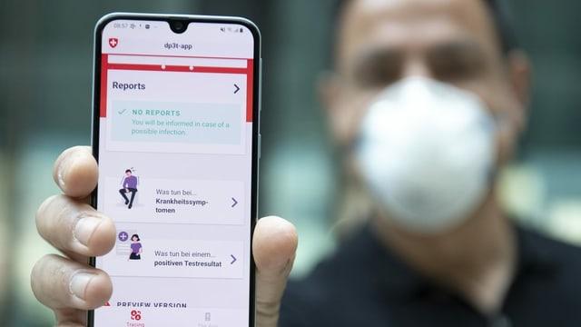 Ein Mann mit Gesichtsmaske hält ein Smartphone in die Kamera, auf der eine App läuft.
