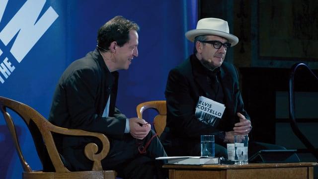 Zwei Männer sitzen auf Stühlen auf der Bühne.