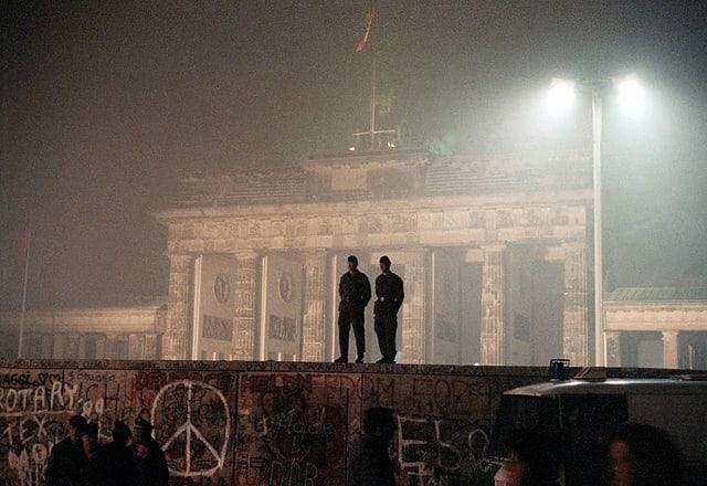 Die Silhouetten von zwei DDR-Grenzsoldaten auf der Berliner Mauer.