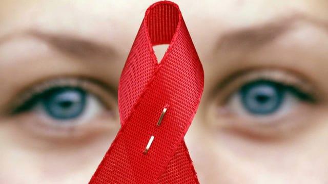 Eine Person hält das Symbol für die Aidsbekämpfung, eine rote Schlaufe, vor ihr Gesicht.