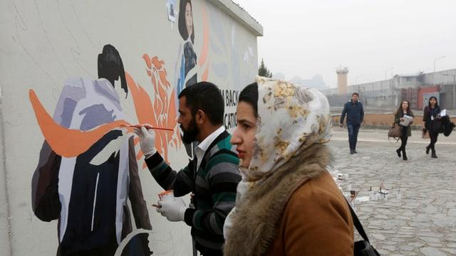 Ein mann und eine Frau vor einer Wandmalerei.