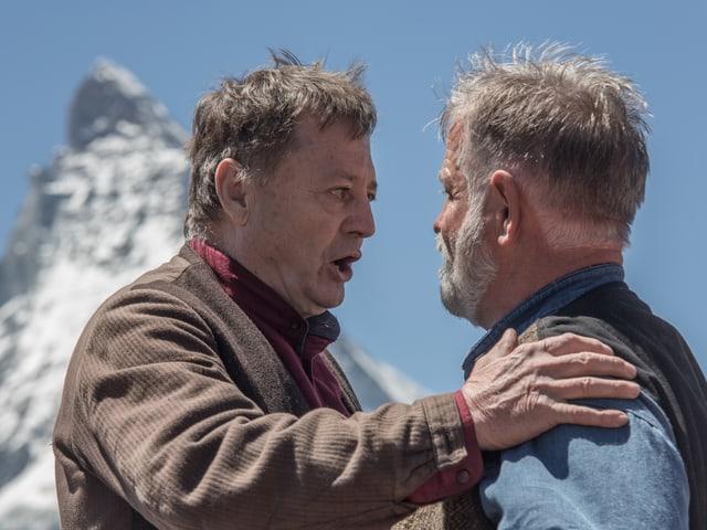 Die beiden Bauern im Theater sprechen miteinander, im Hintergrund das Matterhorn.