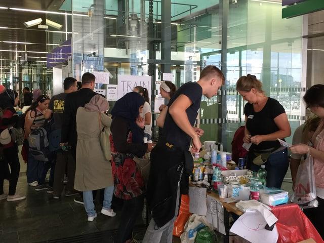 Flüchtlinge stehen vor Tischen mit Spenden