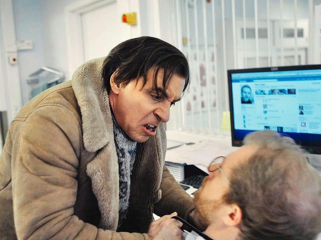 Hauptfigur Frank bedroht einen Büroangestellten.