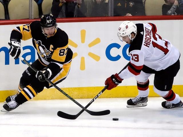 Pittsburgh-Superstar Sidney Crosby (l.) wird von Nico Hischier bedrängt.