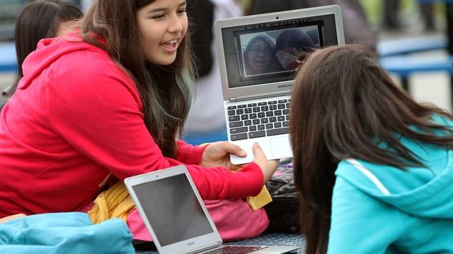 Zwei Mädchen schauen auf einen Laptop.