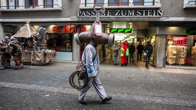 Fasnächtler geht durch eine Strasse in der Luzerner Altstadt