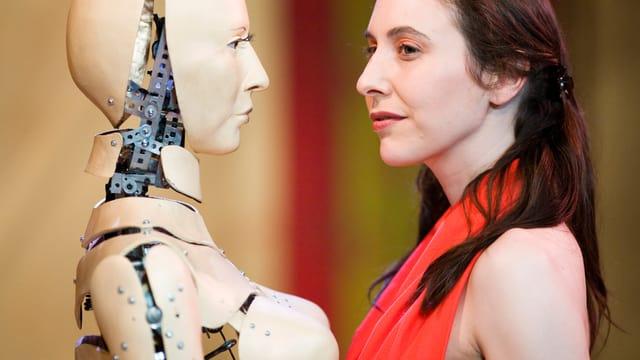 Ein Roboter steht einer Frau in rotem Kleid gegenüber.