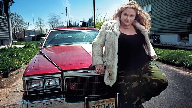 Eine junge Frau lehnt sich an ein rotes Auto.