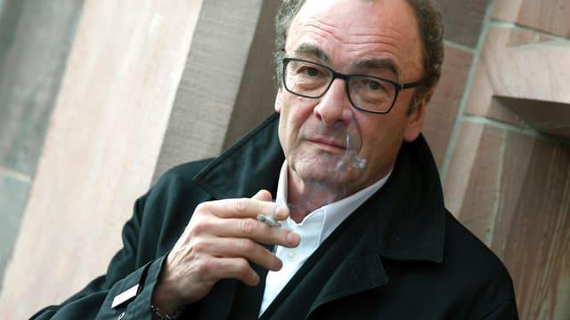 Ein Mann mit Brille und schwarzem Mantel raucht.