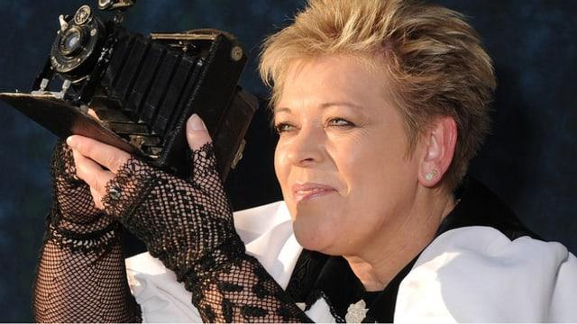 Miriam Schafroth mit antiker Kamera in der Hand.