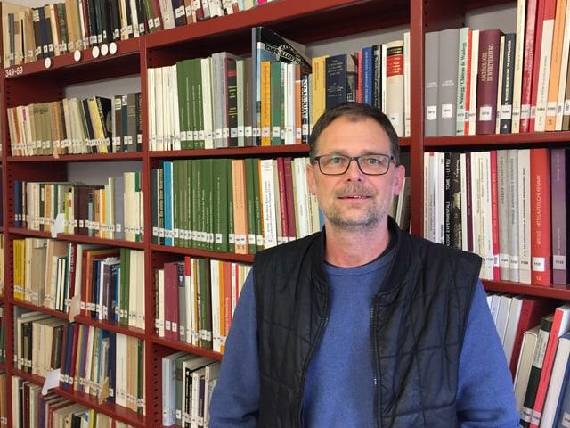 Mann vor Büchergestellt