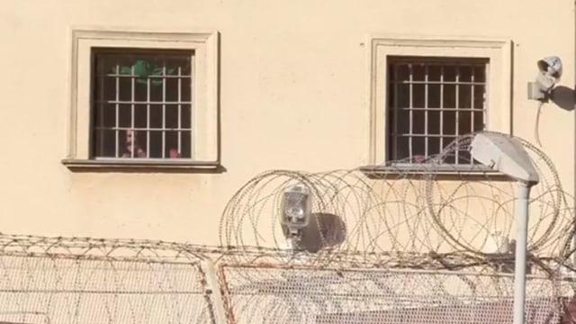Beigfarbene Gefängnismauern hinter Stacheldraht.