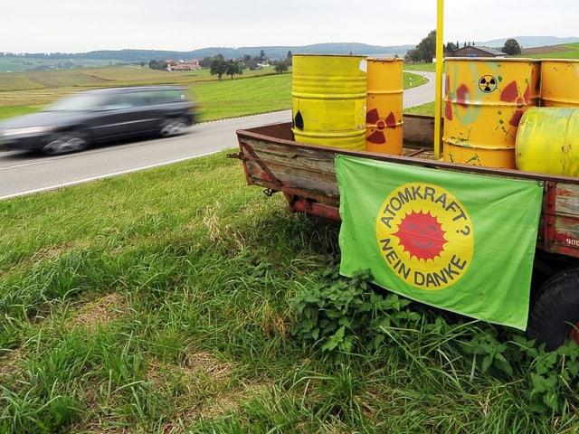 """Autoanhänger mit gelben Atomfässern an einer Landstrasse, Flagge """"Atomkraft, nein Danke"""""""