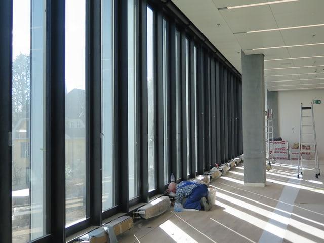 Ein Mann in Arbeitshosen kniet vor einer Fensterfront, im Hintergrund stehen eine Leiter und Baumaterial.