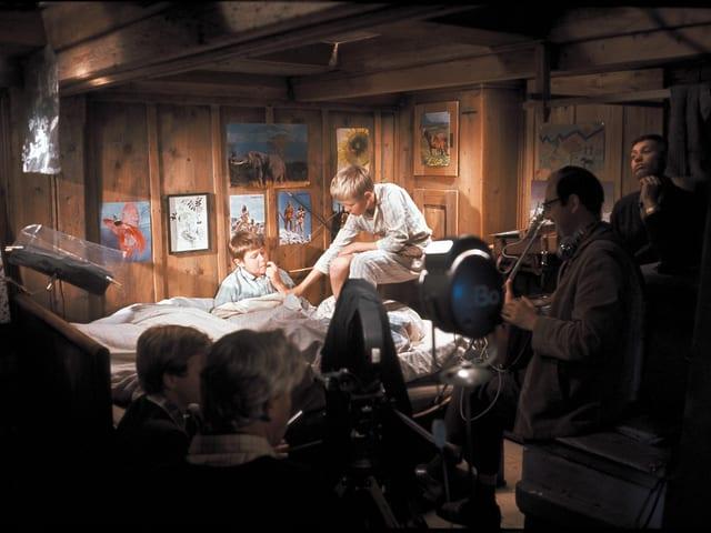 Zwei Kummerbuben Sitzen im Pijama auf dem Bett. Einer von ihnen auf der Lehne. Im Vordergrund Filmscheinwerfer und die Crew.