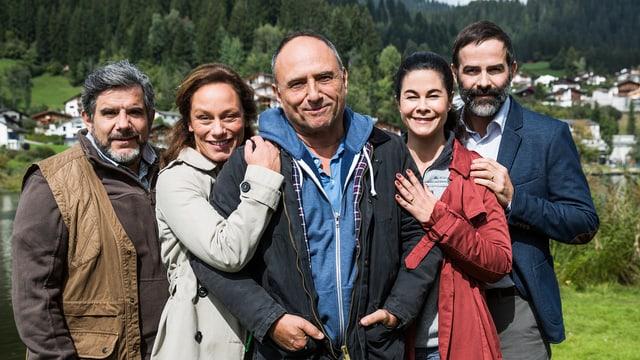 Die fünf Personen posieren lachend vor einem Bergdorf