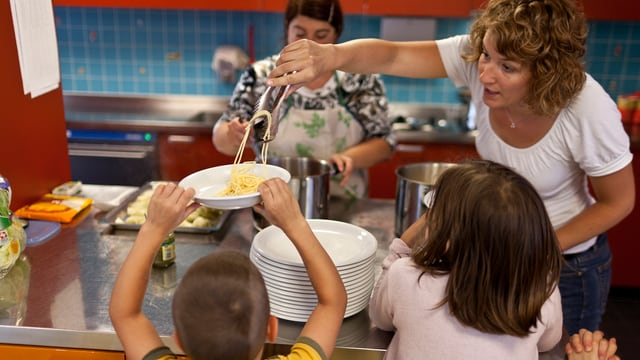 Kinder bekommen Essen in einer Tagesstätte.