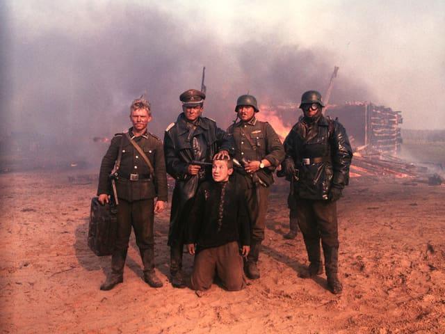 Vier Soldaten richten die Waffe auf einen Jungen Mann, der vor ihnen kauert.