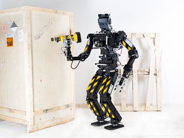 Ein Roboter bohrt mit einem Werkzeug ein Loch in eine Holzwand.