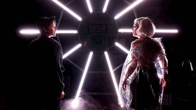 Ein Opernbühnenbild aus leuchtenden Neonröhren, davor zwei Sängerinnen.