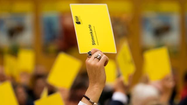 Symbolbild: Hände der BDP-Delegierten halten gelbe Stimmkarten in die Höhe.