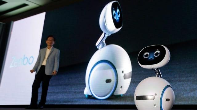 Der Roboter Zenbo steht auf einer Bühne. Im Hintergrund Jonney Shih von Asus.