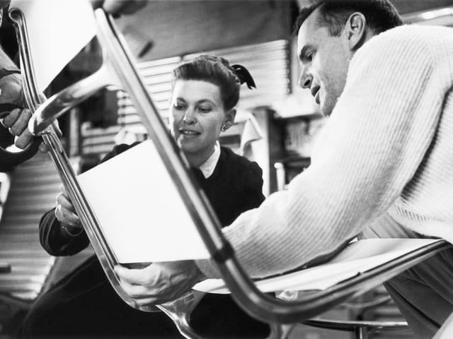Im Vordergrund ist ein Stuhl aus Aluminium mit weisser Lehne und Sitzfläche zu sehen, dahinter und daneben Ray und Charles Eames, die den Stuhl überprüfen.