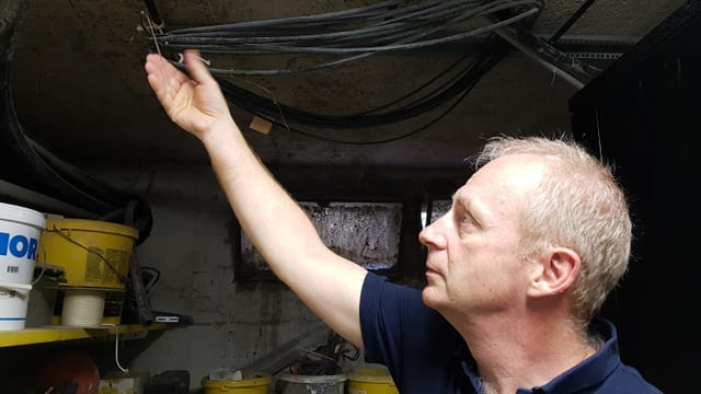 Beat Fahrni im Keller der Winzerei Martin: Hier steht der Verteilkasen des Glasfasernetzes.