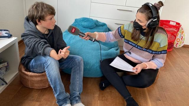 Gaël und Angela sitzen in einem Kinderzimmer auf Sitzsäcken.