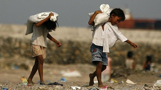 Zwei Kinder schleppen Materialsäcke