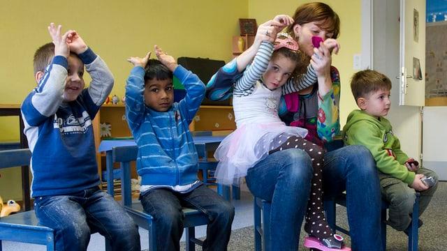Kinder mit Betreuerin auf Stühlen