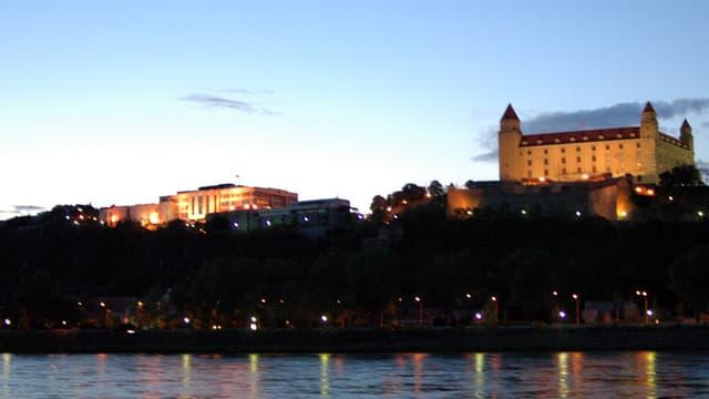 Die beleuchtete Burg in Bratislava in der Dämmerung, im Vorderund ein Fluss.