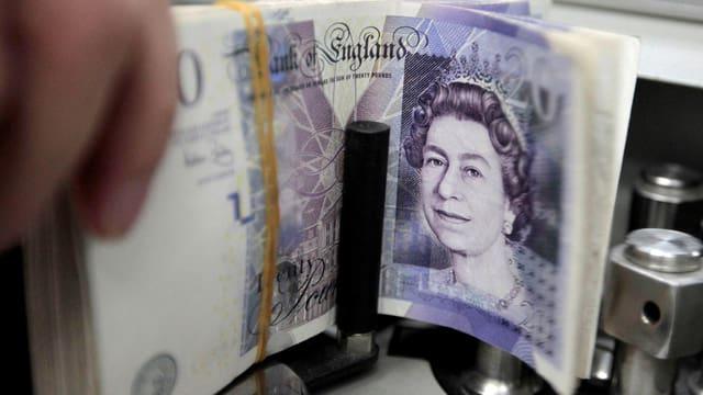Bündel Pfundnoten in einer Geldzählmaschine, gut sichtbar der Kopf der Queen auf der Note
