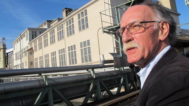 Der Gemeindepräsident von Riedholz schaut kritisch in die Sonne, im Hintergrund das Borregaard-Areal.