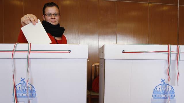 Eine Ungarin wirft ihren Wahlzettel in eine Urne.