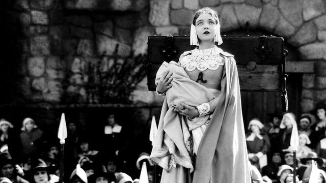 Eine Frau hält ein Baby im Arm. Auf ihrem Kleid ist ein grosses A zu sehen.