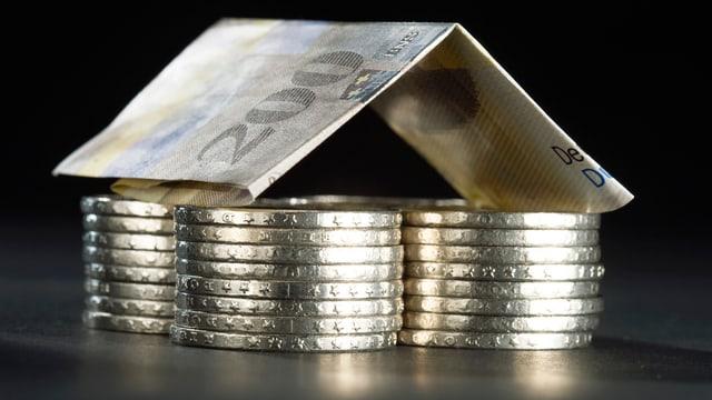 Vier Stapel Fünfliber, darauf gefaltet eine 200-Franken-Note.