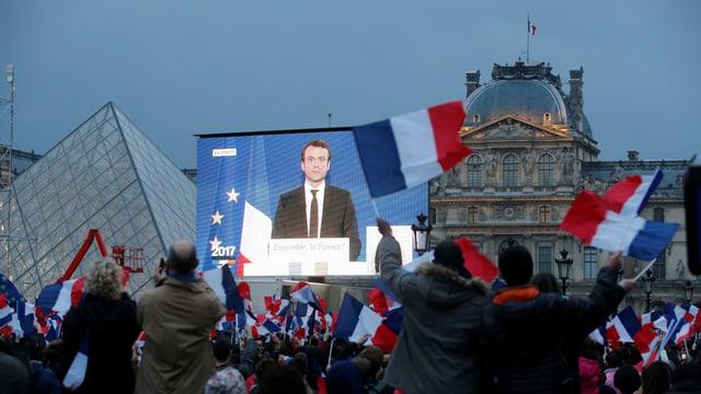 Anhänger verfolgen Macrons Wahlrede auf dem Platz beim Louvre über Grossleindwand.