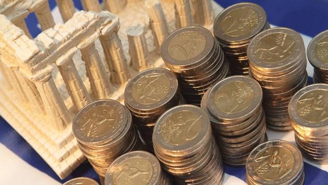 Zu sehen ist eine symbolische Darstellung des Pantheons, vor welchem sich mehrere Stapel Zwei-Euro-Münzen häufen.