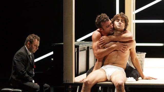 Auf der Bühne umarmen sich zwei Männer mit nacktem Oberkörper, neben ihnen ein Mann im Anzug am Klavier.